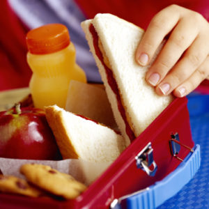 child taking sandwich out of lunch box