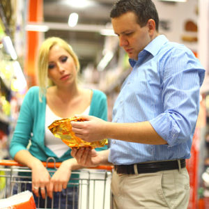 couple reading food label in grocery store