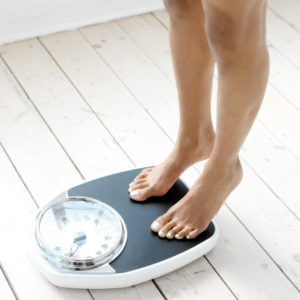 woman standing on tip toes on a weighing scale